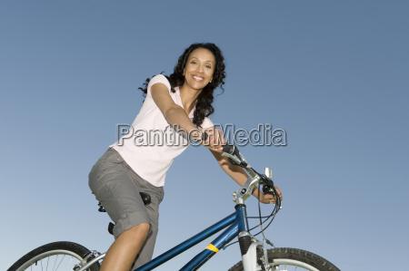 female cycling against clear blue sky