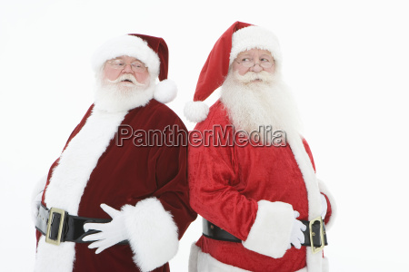 two santa claus standing back to