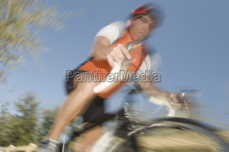 man riding cycle against blue sky