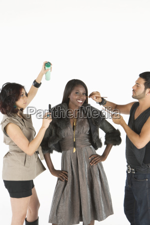 two makeup artists assisting model