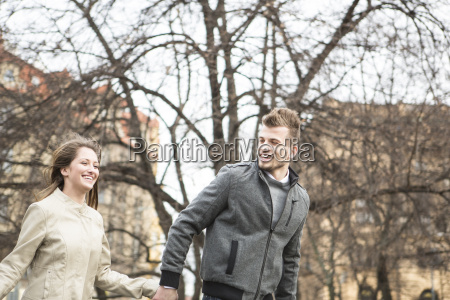 smiling young man and woman holding