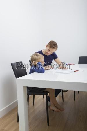 mid adult man helping boy in