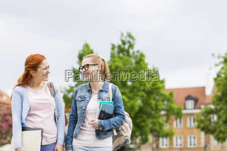 smiling young female college friends walking