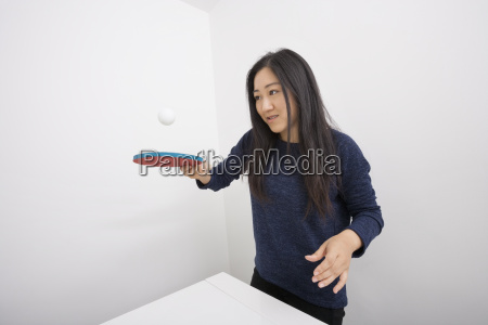 female table tennis player bouncing ball