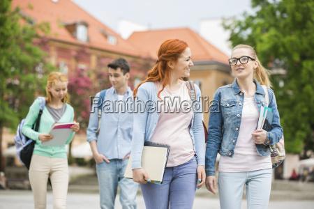 junge universitaetsfreunde die auf strasse gehen
