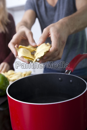 midsection of man cooking pasta