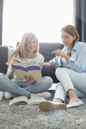 mother assisting daughter in homework at