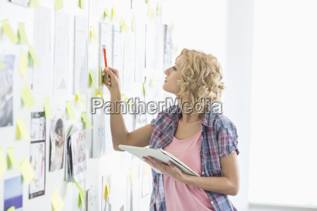 creative businesswoman analyzing papers stuck on