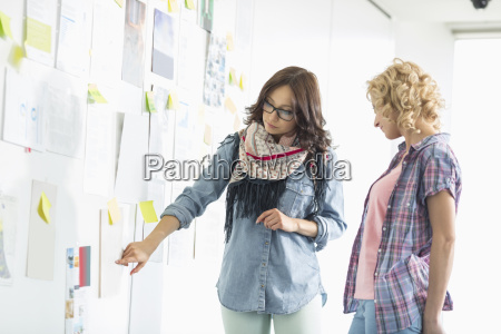 businesswomen discussing over papers stuck on