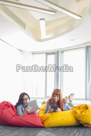 businesswomen using digital tablets while relaxing