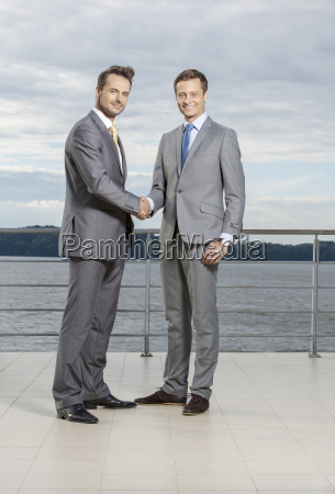 full length portrait of businessmen shaking