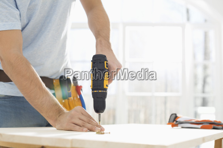 midsection of man drilling nail on