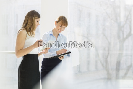 smiling businesswomen with tablet pc and