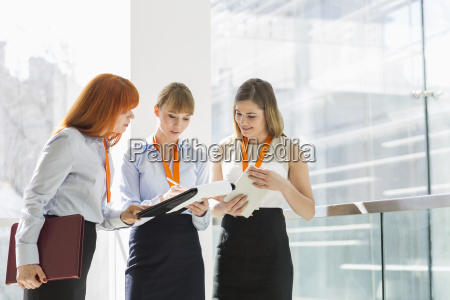 businesswomen doing paperwork by railing in