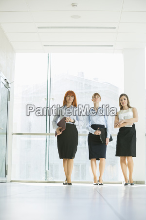 full length of confident businesswomen standing
