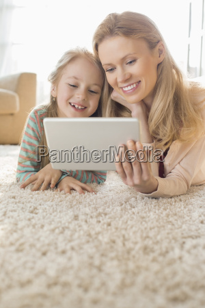 happy mother and daughter using digital
