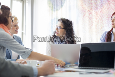 happy businesspeople discussing during meeting in