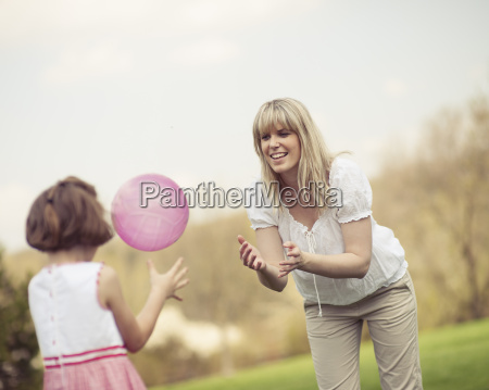 mother throwing ball to daughter in