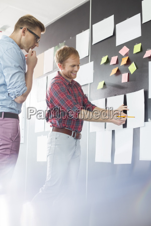 creative businessmen discussing over document on