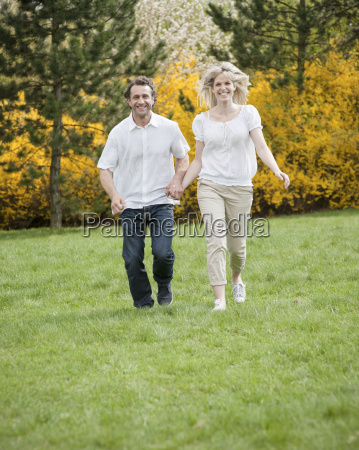 couple running through park holding hands