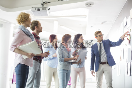 businesspeople discussing over documents on wall