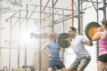 people assisting man in lifting barbell