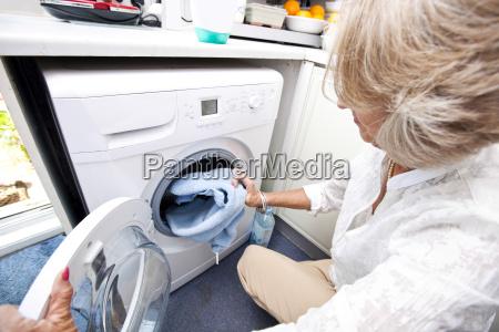 aeltere frau laedt handtuch in der