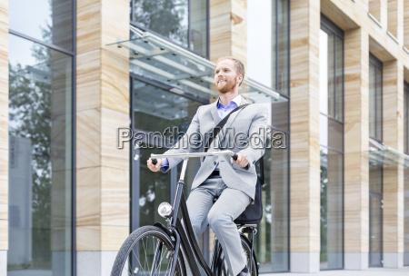 laechelnde geschaeftsmann faehrt fahrrad ausserhalb des