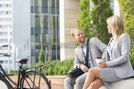 happy businessman talking to female colleague
