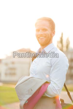 portrait of happy businessman standing outdoors