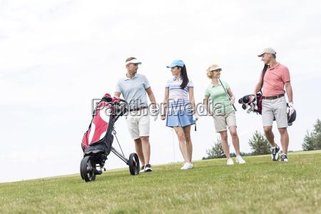 sprechende freunde beim gehen am golfplatz