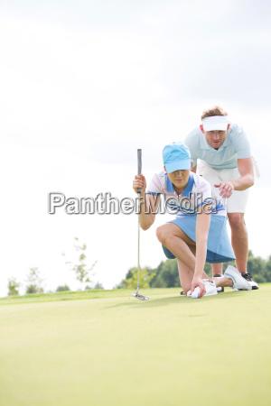 man assisting woman placing ball on