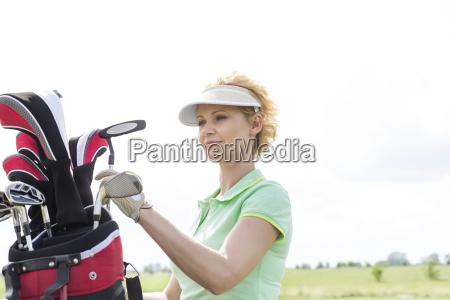 female golfer with golf club bag