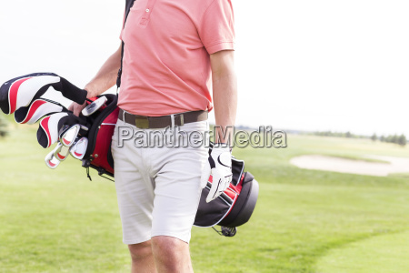 midsection of man with golf club
