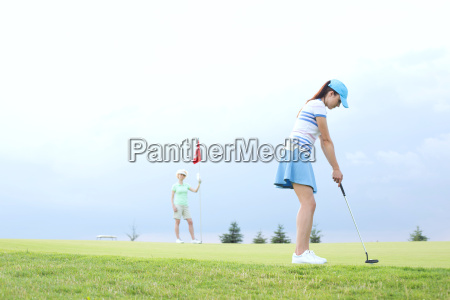 woman playing golf with female friend