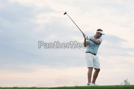 mid adult man playing golf against