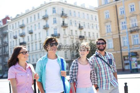 happy male and female friends walking
