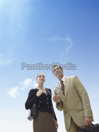 business man and woman standing against
