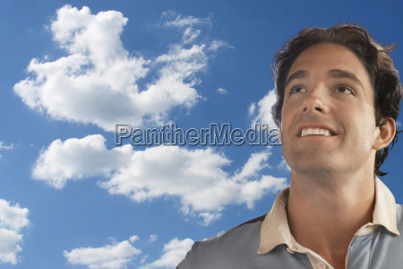 smiling young man daydreaming against cloudy