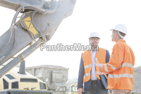 engineers discussing at construction site against