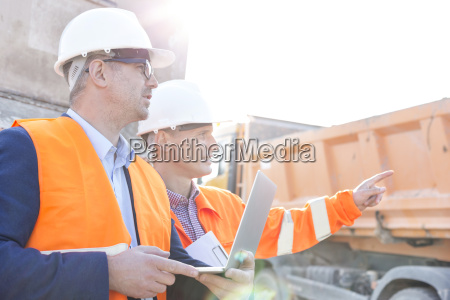 supervisor showing something to colleague holding