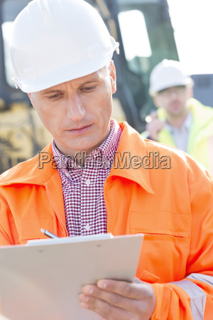 supervisor writing on clipboard at construction