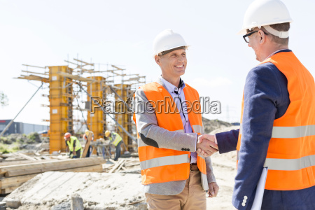 engineers shaking hands at construction site