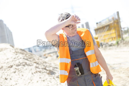 tired construction worker wiping forehead at