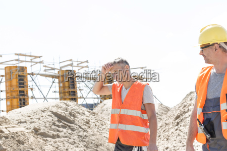 construction worker looking at tired colleague