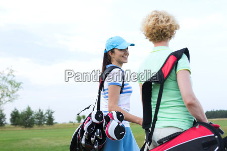 smiling female golfer talking to friend