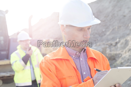 engineer writing on clipboard at construction