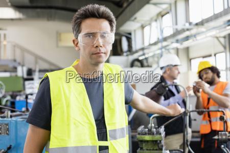 portraet von mitte erwachsenen arbeiter tragen