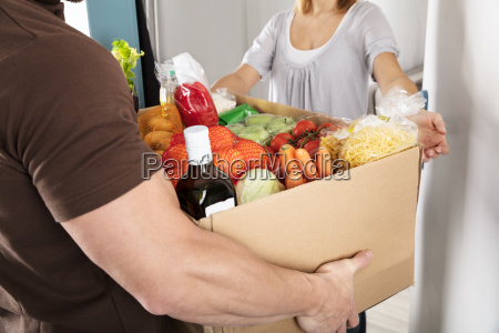 lieferung mann giving grocery box to
