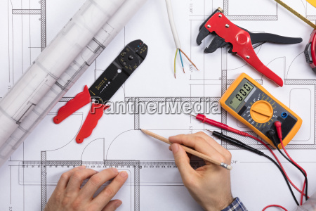 architect drawing plan on blueprint with